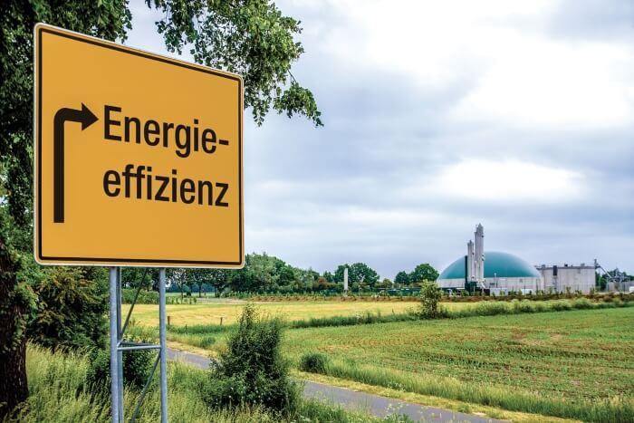 Schild mit Aufschrift Energieeffizienz führt zu einem Blockheizkraftwerk