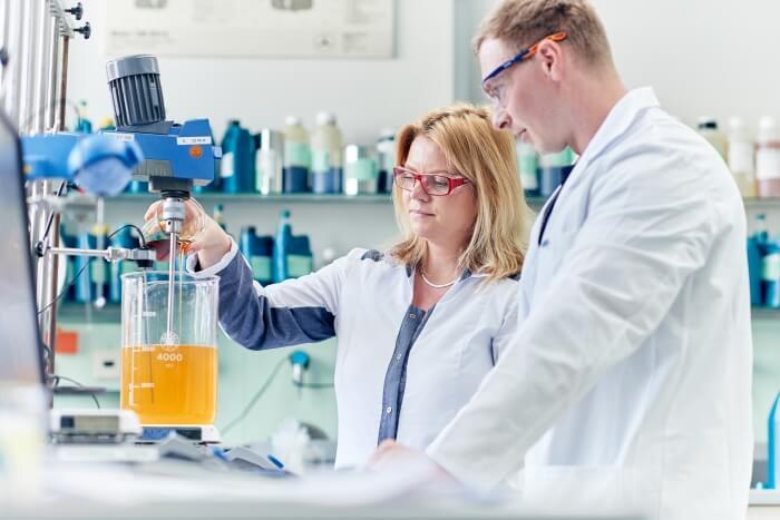 Zwei Laboranten stellen einen Schmierstoff zusammen