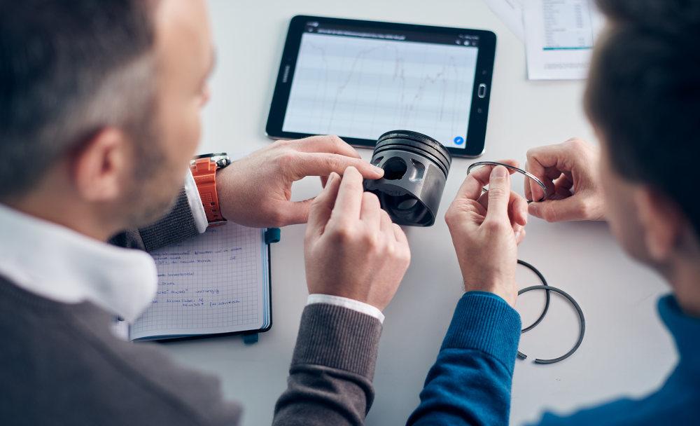 ADDINOL Mitarbeiter bei der Entwicklung von Gasmotorenölen mit Hilfe von Motorenkomponenten und Tablet.