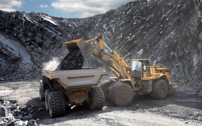 Bagger kippt Kohle aus im Bergbau mit Hydraulik