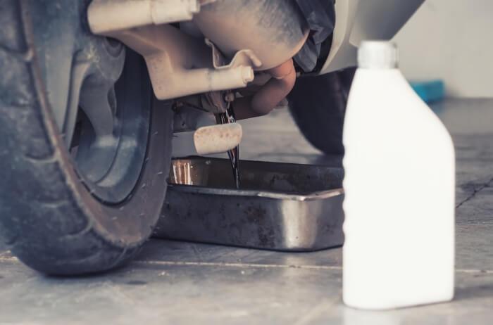 Ölwechsel beim Motorrad, Motoröl wird in Auffangschüssel abgelassen