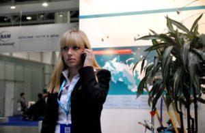 Mitarbeiterin von ADDINOL steht telefonierend vor einer Messewand.